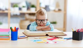 Funny child  boy  doing homework writing and reading at home. A funny child  boy  doing homework writing and reading at home stock photography