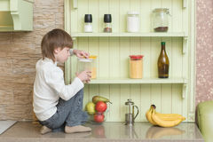 Funny child boy sitting on kitchen table Royalty Free Stock Photo