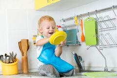 Funny child boy sitting on kitchen table and washing dish. Funny child little boy sitting on kitchen table and washing dish Stock Images