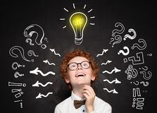 Funny child boy student with lightbulb. Brainstorming and idea concept.  stock images
