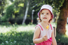 Funny child with candy lollipop, happy little girl eating big Stock Photos