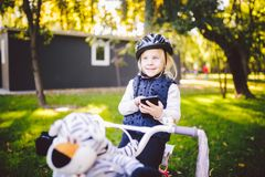 Funny child Caucasian girl blonde in a bicycle helmet near a purple bike with a basket in outside the park on a green royalty free stock photos