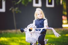 Funny child Caucasian girl blonde near a purple bike with a basket and a zebra toy in an outside park on a green lawn grass cart. At home royalty free stock image