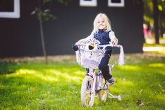 Funny child Caucasian girl blonde near a purple bike with a basket and a zebra toy in an outside park on a green lawn. Grass cart at home stock photography