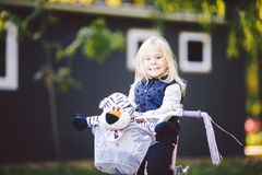 Funny child Caucasian girl blonde near a purple bike with a basket and a zebra toy in an outside park on a green lawn. Grass cart at home royalty free stock images