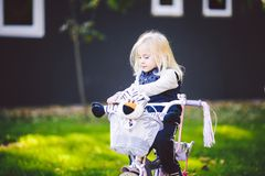 Funny child Caucasian girl blonde near a purple bike with a basket and a zebra toy in an outside park on a green lawn grass cart. At home royalty free stock photos