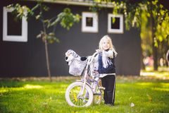 Funny child Caucasian girl blonde near a purple bike with a basket and a zebra toy in an outside park on a green lawn. Grass cart at home stock photos
