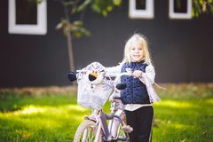 Funny child Caucasian girl blonde near a purple bike with a basket and a zebra toy in an outside park on a green lawn grass cart. At home royalty free stock photo