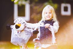 Funny child Caucasian girl blonde near a purple bike with a basket and a zebra toy in an outside park on a green lawn grass cart. At home royalty free stock photography
