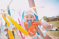 Funny child, the child smiles with a pacifier in his mouth. On the street, in the hands of the mother, among the Royalty Free Stock Photography