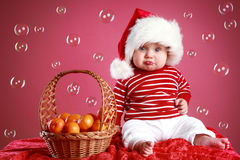 Funny Child in a Christmas red cap Royalty Free Stock Photos