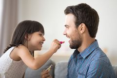 Funny child daughter applying lipstick on dads lips doing makeup royalty free stock photo