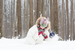 Funny child digging in the snow Royalty Free Stock Images
