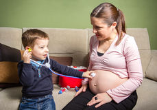 Child doctor examining his pregnant mother Stock Images