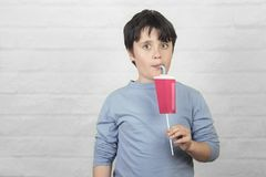 Funny child drinking smoothie royalty free stock photography