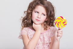 Funny child eat candy lollipop, little girl eating sweets, studio Stock Images
