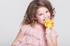 Funny child eat candy lollipop, little girl eating sweets, studio Royalty Free Stock Photo