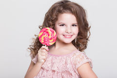 Funny child eat candy lollipop, little girl eating sweets, studio Royalty Free Stock Images