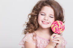 Funny child eat candy lollipop, little girl eating sweets, studio Stock Photos
