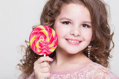 Funny child eat candy lollipop, little girl eating sweets, studio Royalty Free Stock Photos
