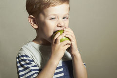 Funny Child eating apple.Little Boy with green apple. Health food. Fruits Royalty Free Stock Photos