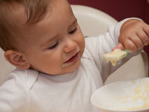 Funny child eating and holding spoon Royalty Free Stock Photo