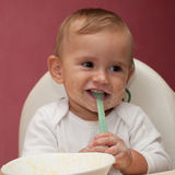 Funny child eating and holding spoon Stock Images