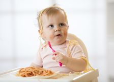 Funny child eating noodle. Grimy kid eats spaghetti with fork sitting on table at home Royalty Free Stock Image