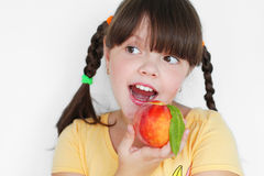 Funny child eating peach, portrait closeup Royalty Free Stock Photos