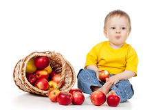 Funny child eating red apple. Funny child with basket filling red apples Stock Image