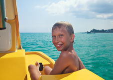Funny child enjoying summer vacation on yellow rowing boat Royalty Free Stock Photography