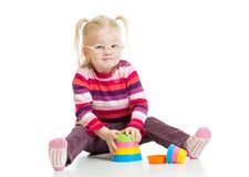 Funny child in eyeglases playing colorful pyramid Stock Photo