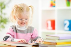 Funny child in eyeglases reading book at home Stock Photography