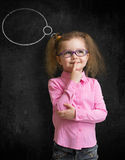 Funny child in eyeglasses standing near school chalkboard. And thinking Royalty Free Stock Photos
