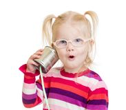 Funny child in eyeglasses using a can as a. Telephone isolated on white Royalty Free Stock Photo