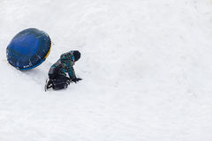 Funny child falling from the snowy mountains with tubing in the winter Stock Images