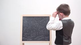 Funny child focus on chalk board with math scribble, exhausted student with eyeglasses and uniform, heavy learning. UHD 4K stock video