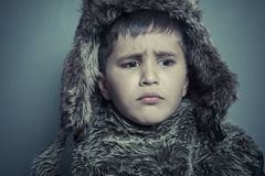 Funny child with fur hat and winter coat, cold concept and storm Stock Images