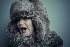 Funny child with fur hat and winter coat, cold concept and storm Stock Photos