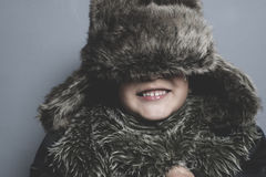 Funny child with fur hat and winter coat, cold concept and storm Royalty Free Stock Photography