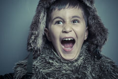 Funny child with fur hat and winter coat, cold concept and storm Royalty Free Stock Images