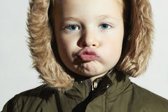 Funny child in fur hood and winter jacket. fashion kids.children Royalty Free Stock Images