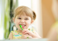 Funny child girl brushing teeth royalty free stock photos