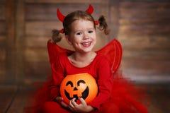 Funny child girl in devil halloween costume on  dark wooden back Stock Images