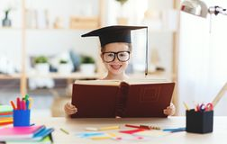 Funny child  girl  doing homework writing and reading at home royalty free stock image