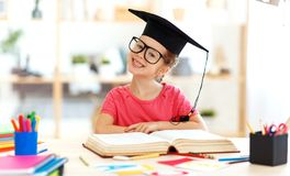 Funny child  girl  doing homework writing and reading at home royalty free stock photography