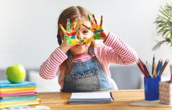 Funny child girl draws laughing shows hands dirty with paint. Happy funny child girl draws laughing shows hands dirty with paint Stock Photography