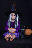 Funny child girl dressed witch costume with pumpkin. Halloween holidays concept. Royalty Free Stock Image