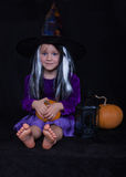 Funny child girl dressed witch costume with pumpkin. Halloween holidays concept. Royalty Free Stock Photography