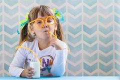 Funny child girl drinking milk with glasses straw on blue background. Growing up concept. stock image